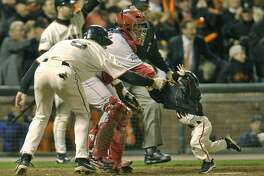 San Francisco Giants' J.T. Snow, left, drags 3-year-old Darren Baker, son of Giants manager Dusty Baker, away from homeplate and the path of oncoming baserunner David Bell after scoring in the seventh inning of Game 5 of the World Series in San Francisco, Thursday, Oct. 24, 2002. Angels catcher Bengie Molina and homeplate umpire Mike Reilly are at rear. (AP Photo/Kevork Djansezian)