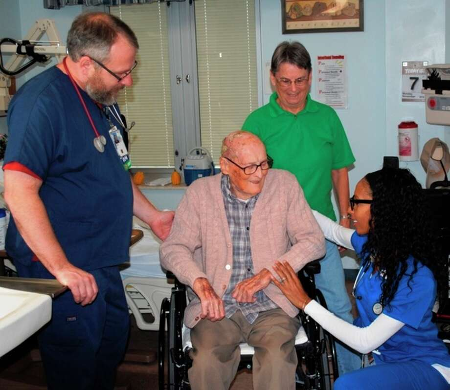 Photo provided Veteran Lewis Wolfe and his daughter, Judy Vader, engage with the care team at the Aleda E. Lutz VA.