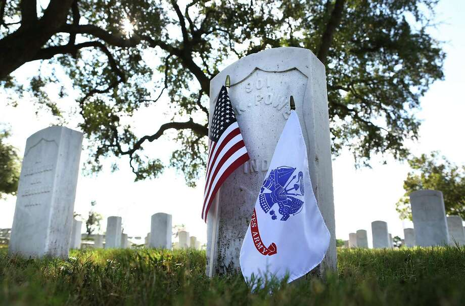 An Army and American flag adorn the grave of James K. Powers of Indiana who died in 1914, at the San Antonio National Cemetery. A Veterans Day Commemorative Ceremony presented by the Bexar County Buffalo Soldiers was held at the site, Friday, Nov. 11, 2016. Photo: Bob Owen, Staff / San Antonio Express-News / ©2016 San Antonio Express-News
