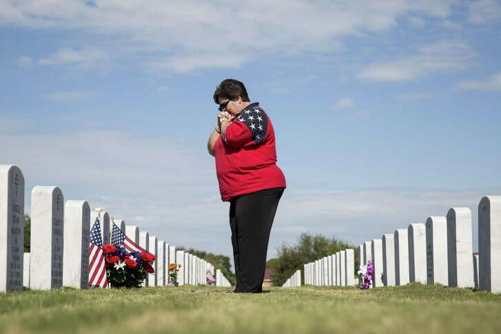 Judy Carlile visits her husband's headstone after the Veterans Day ceremony at Fort Sam Houston National Cemetery in San Antonio, Texas on November 11, 2016. Her husband Jim Carlile was a Vietnam veteran who spent 23 years in the Air Force, but passed away eight years ago.