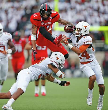 UT's John Bonney, right, gets in on the action when Texas Tech's Derrick Willies tries to go over the top. Photo: Brad Tollefson, MBI / Lubbock Avalanche-Journal