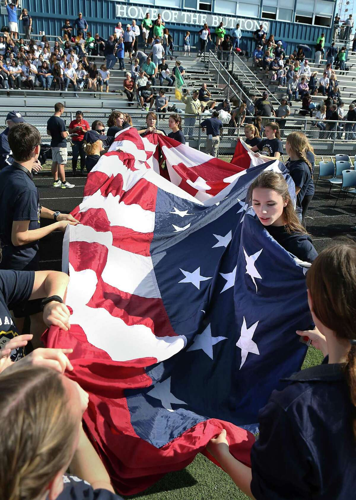 Members of the Notre Dame Marching Band fold a large American flag as the band rehearsed and mentored Central Catholic High School students at the school on Nov. 11, 2016.