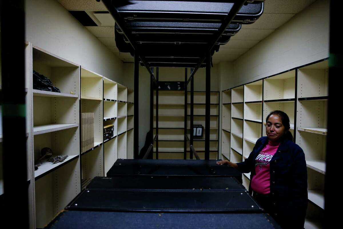 Elsik High School band director Brenda Corral-Smith on Friday inspects a storage closet where someone stole 29 high-quality instruments earlier this month.