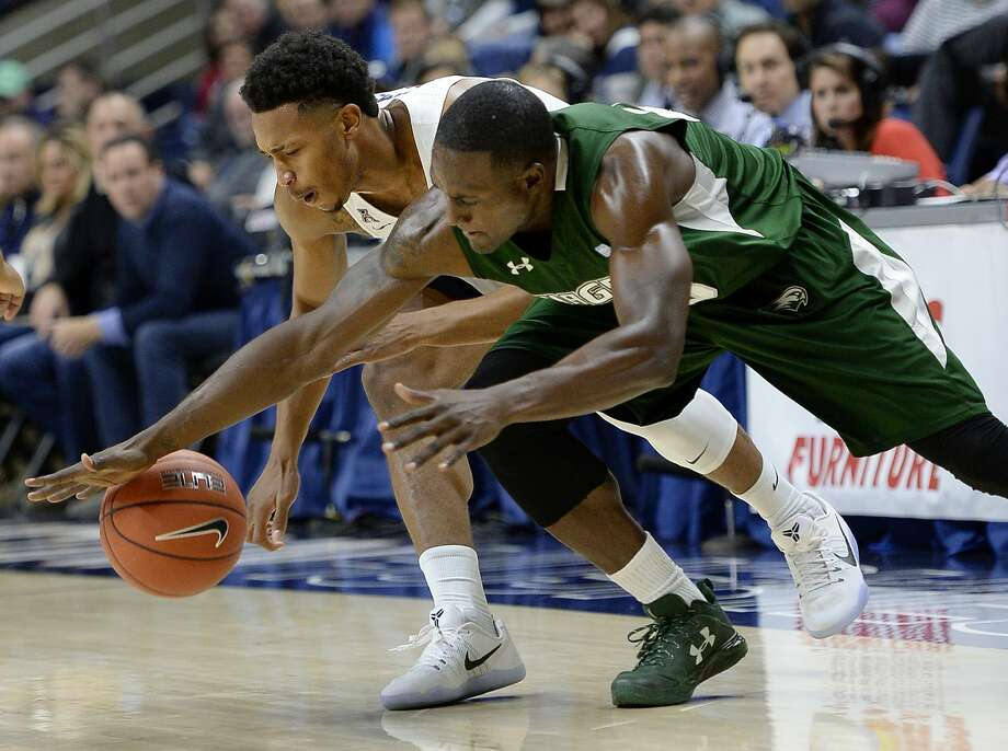 Connecticut's Jalen Adams, left, and Wagner's Michael Carey drive for a loose ball during the first half of an NCAA college basketball game, Friday, Nov. 11, 2016, in Storrs, Conn. (AP Photo/Jessica Hill) Photo: Jessica Hill