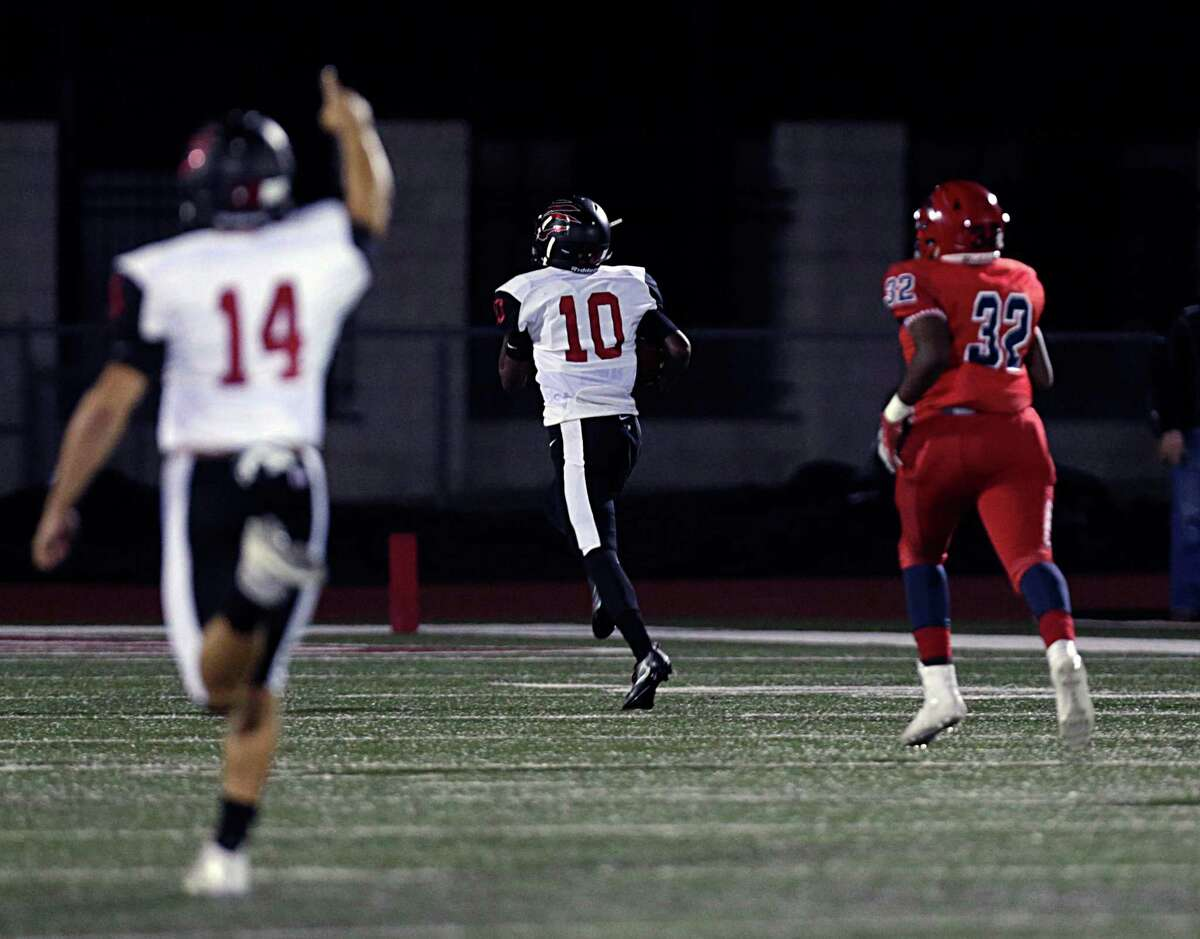 Clear Brook's quarterback Jaizac Garcia left, cheers on teammate Mark Mitlon center, as he breaks away from Dawson's Joel Mitchell right, to score a touchdown during the first half of Class 6A, Division II bi-district playoffs at Pearland High School Stadium Nov. 11, 2016, in Pearland.
