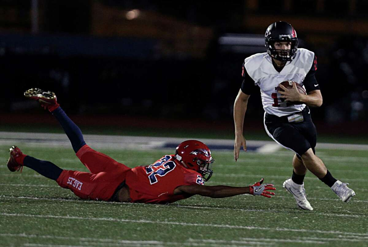 Clear Brook's quarterback Jaizac Garcia right, breaks away from Dawson's Alec Prince right, during the first half of Class 6A, Division II bi-district playoffs at Pearland High School Stadium Nov. 11, 2016, in Pearland.