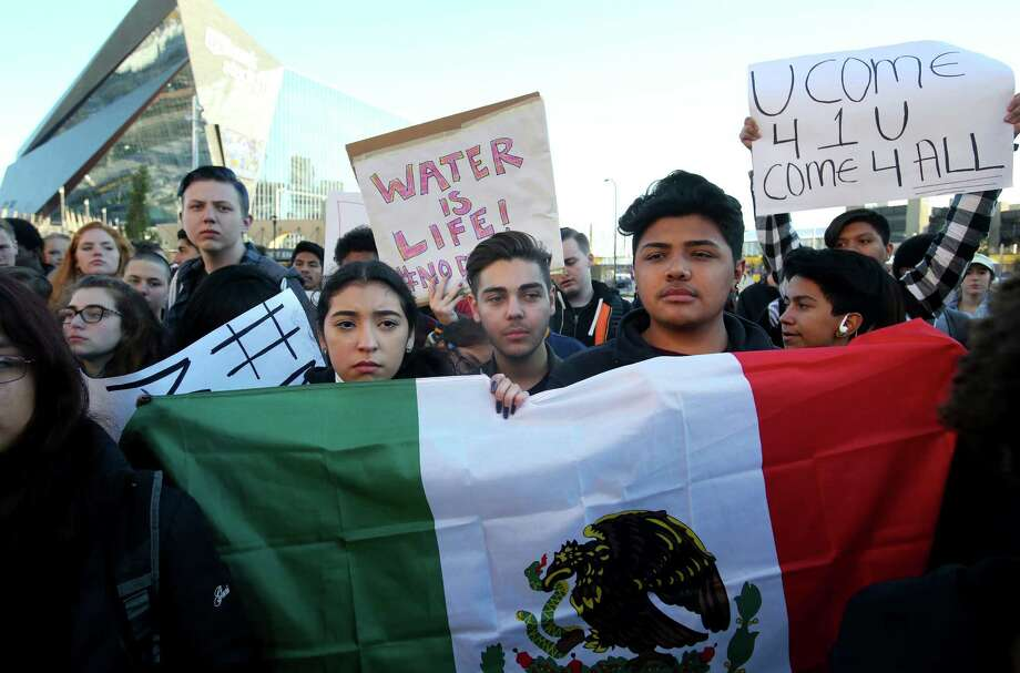 Latino Edison High students Saira Gudiel, from left, Oguzhan Akguen and Cesar Carrillo, carrying the Mexican flag, join other students from metro area high schools march down Cedar Avenue in protest against President-elect Donald Trump, outside the US Bank Building in Minneapolis on Friday, Nov. 11, 2016. (David Joles/Star Tribune via AP) ORG XMIT: MNMIT101 Photo: David Joles / David Joles