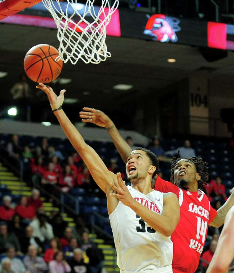 Fairfield University's Curtis Cobb lays up the ball as Sacred Heart University's Chris Robinson tries to defend during men's college basketball action at the Webster Bank Arena in Bridgeport, Conn. on Friday Nov. 11, 2016. Photo: Christian Abraham / Hearst Connecticut Media / Connecticut Post