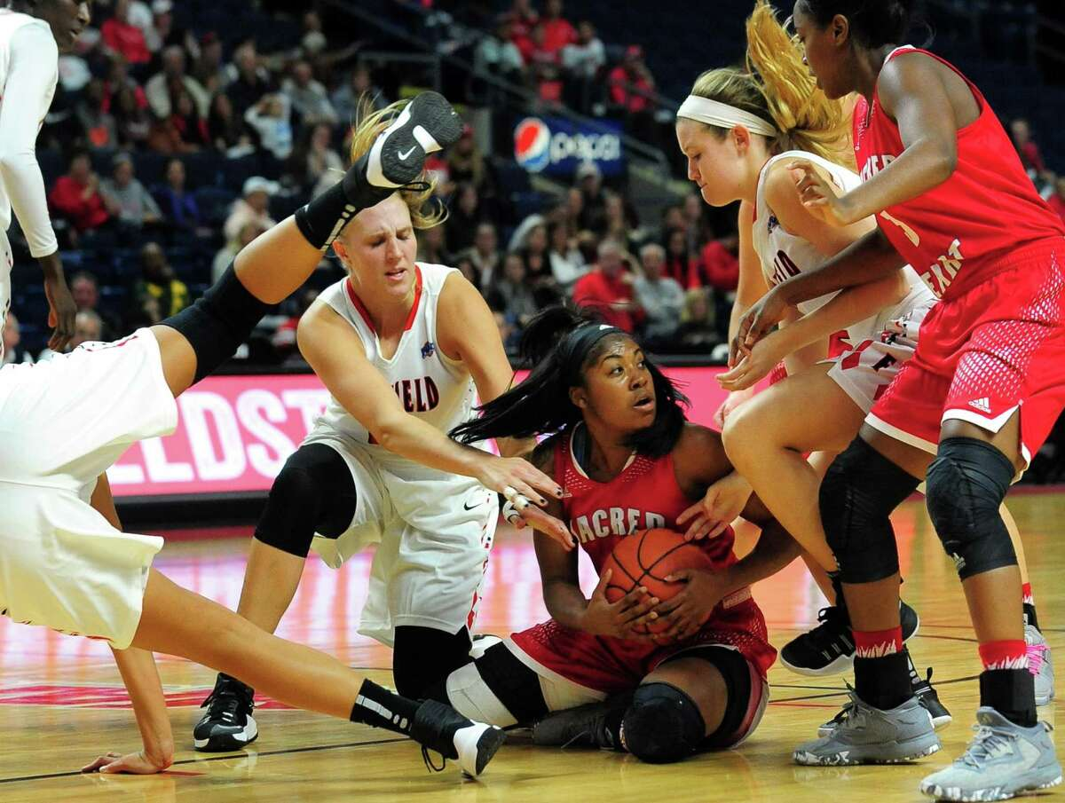 Sacred Heart University's Tykera Carter holds onto a rebound as Fairfield University players converge on her during women's college basketball action at the Webster Bank Arena in Bridgeport, Conn. on Friday Nov. 11, 2016.