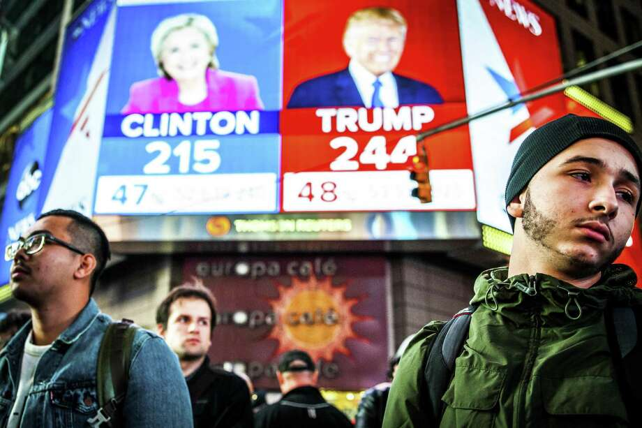 People watch election results at Times Square in New York, Nov. 9, 2016. Clinton has followed Al Gore as the second Democratic presidential candidate in modern history to be defeated by a Republican who earned fewer votes, in his case by George W. Bush. Even President-elect Donald Trump, who won the electoral vote but lost the popular vote, called the system a disaster for a democracy in 2012. Photo: George Etheredge /The New York Times / NYTNS