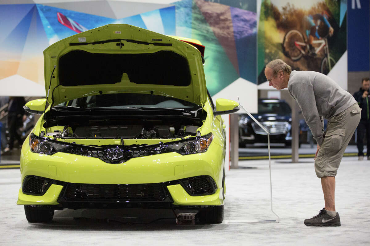 A man reads specs on a 2017 Toyota Corolla.