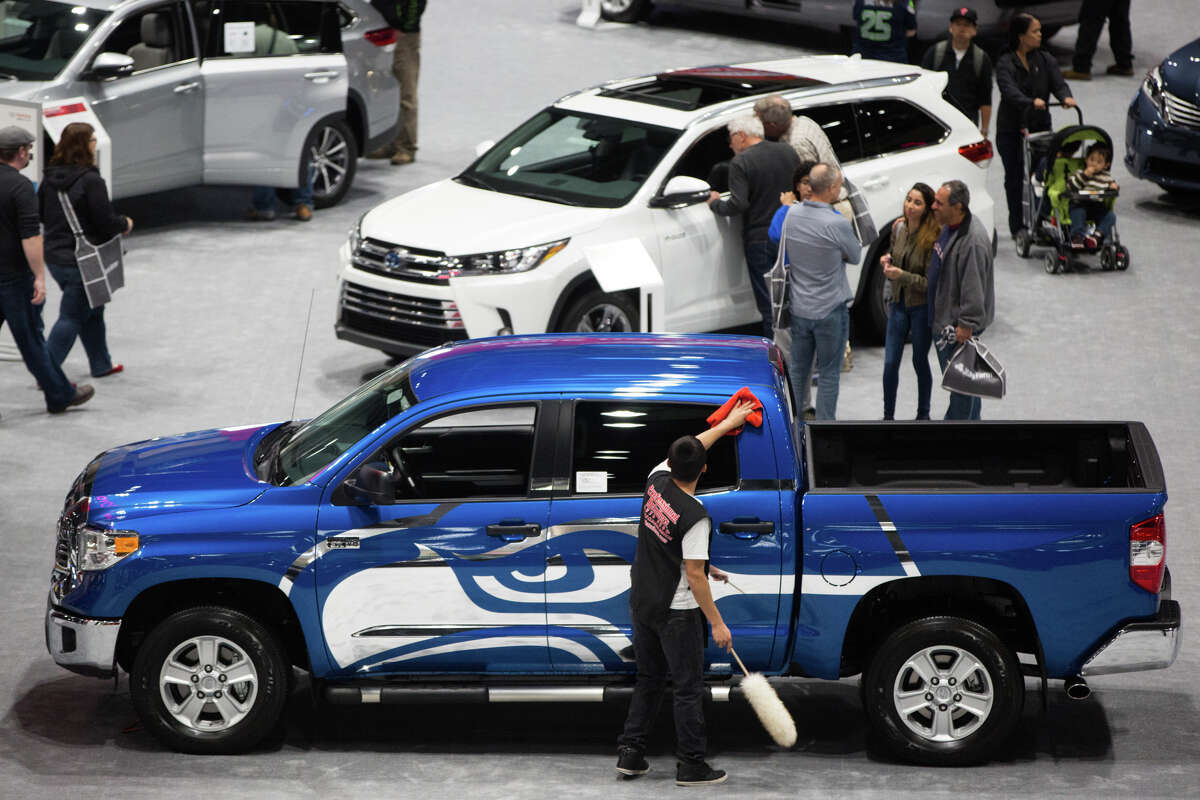 A worker wipes down a Seahawks-themed Toyota Tundra.