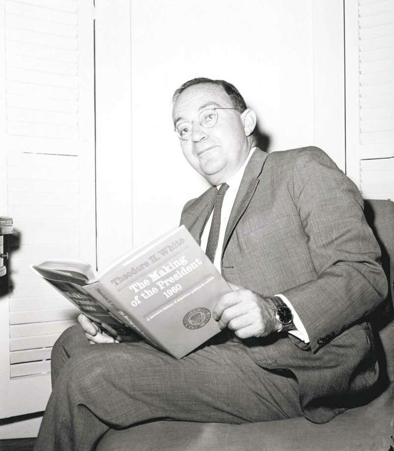 """Author Theodore H. White poses in his New York City apartment with the book that won him the Pulitzer Prize on May 7, 1962, """"The Making of a President 1960."""" In the book, White explores how Republicans and Democrats looked to Connecticut results on Election Day 1960 for early signals of the eventual outcome. Photo: AP File Photo"""