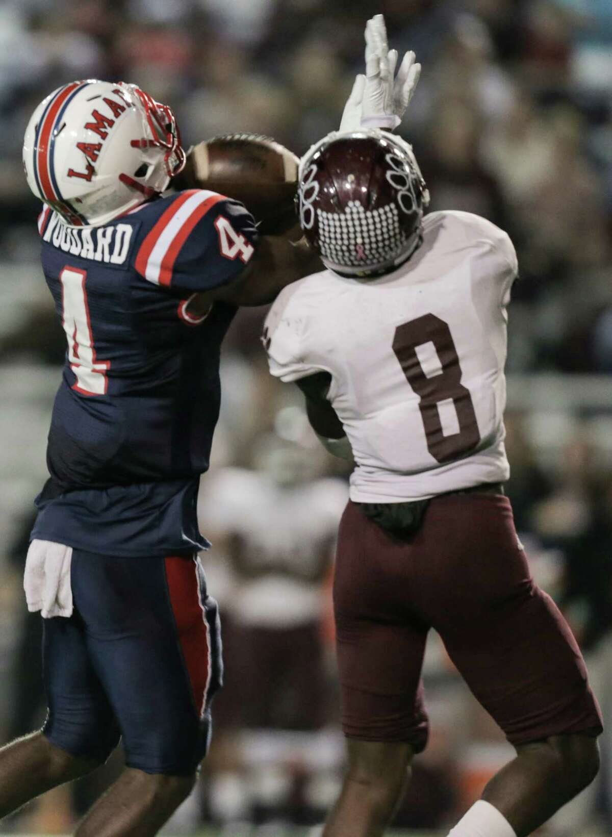 Lamar's Al'Vonte Woodard (4) catches a long pass against Cy-Fair's Erick Hallett (8) in the fourth quarter of Class 6A, Division 1 bi-district high school playoffs on Friday, Nov. 11, 2016, in Houston. Lamar won the game 15-14.