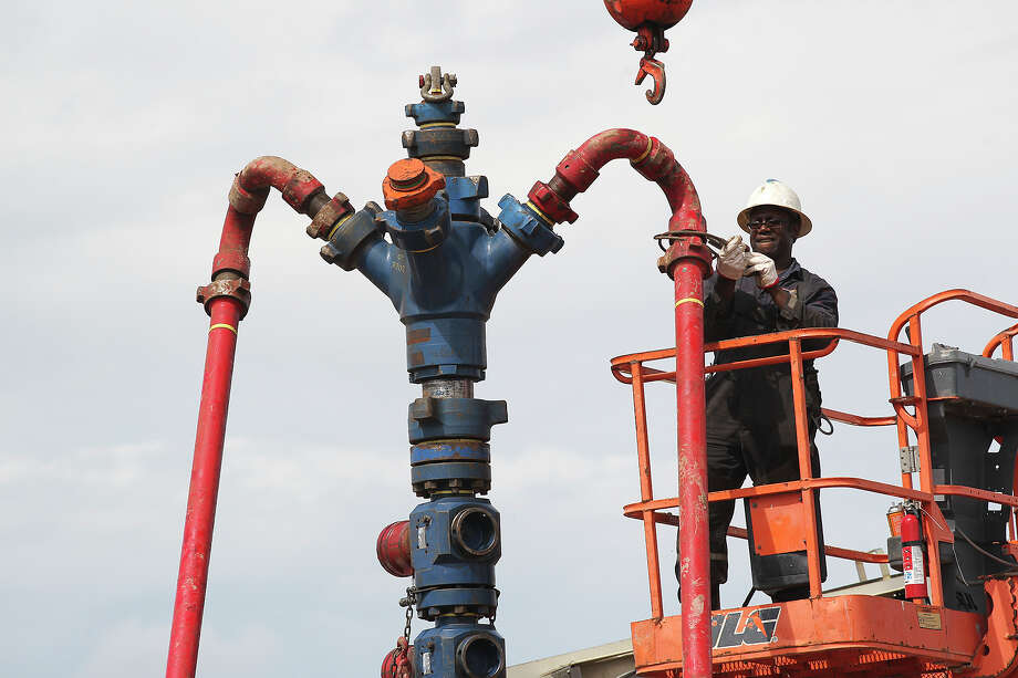 Nathen George removes pipes from a frac tree at a well on a ranch southwest of Ben Bolt. Fracturing produces millions of gallons of wastewater. Photo: Jerry Lara, Staff / ©2013 San Antonio Express-News