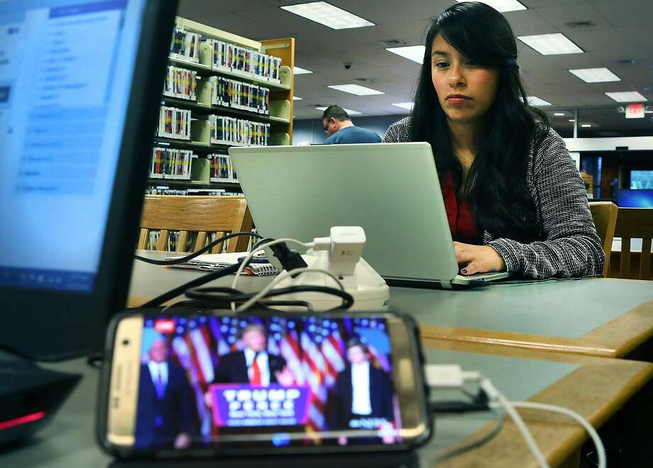Yessica C. Vazquez, 25 years old, studies for a political science class on Wednesday, Nov. 9, 2016, at the Westfall Library, next to another student who had her cell phone playing Trump's acceptance speach.  Vazquez plans to go to St. Mary's Law School. Photo: Bob Owen, San Antonio Express-News