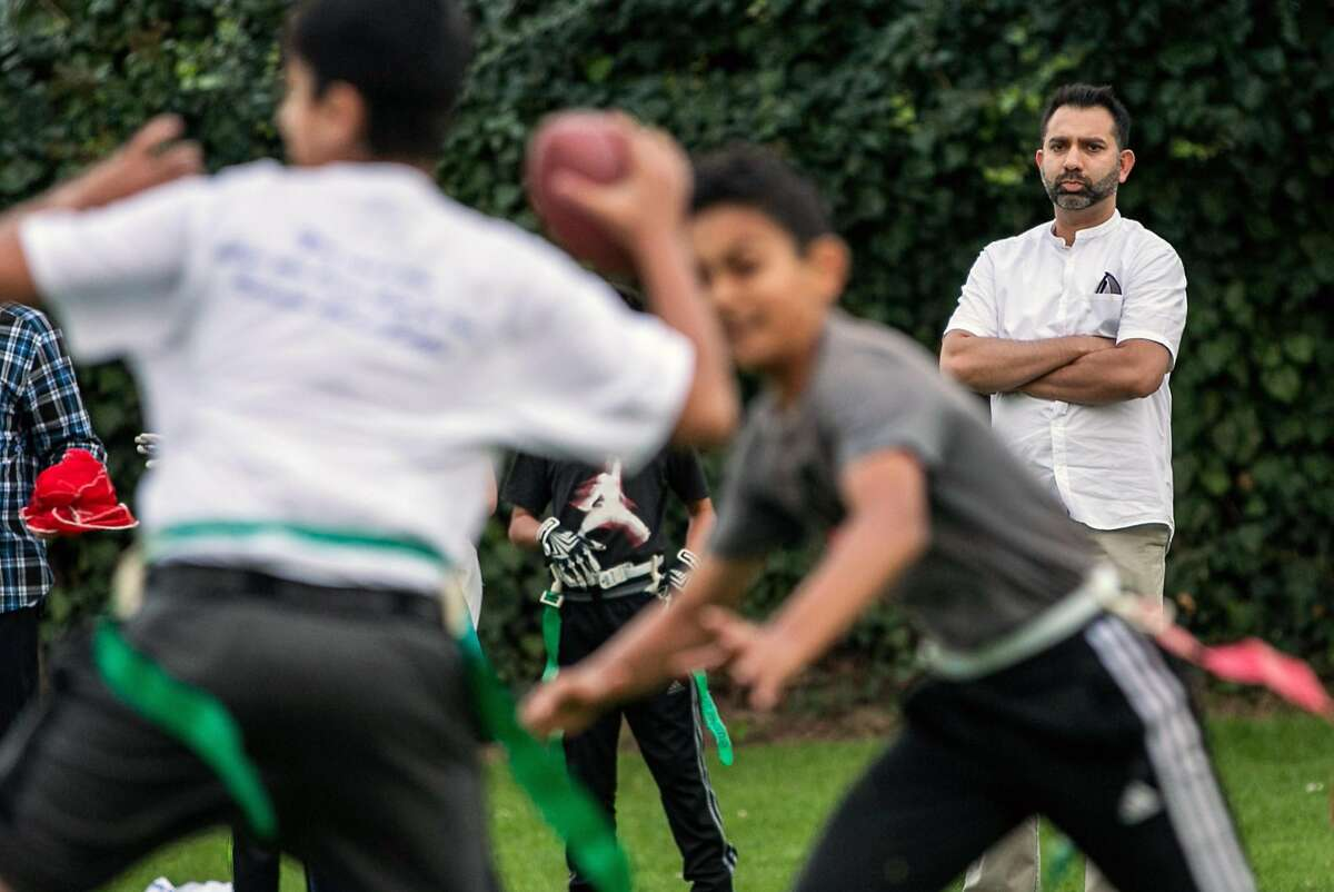 Right: Noman Munif checks out the flag football game, during the Northstar Ilm Tree Sports Day on Friday, Nov. 11, 2016 in Union City, Calif. His sons participate in the games.