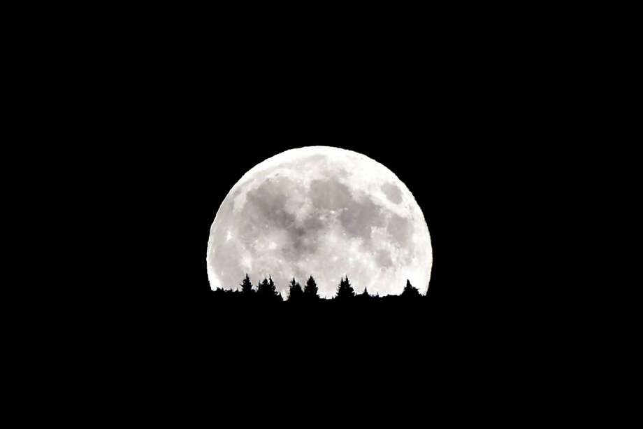 """(FILES) This file photo taken on August 10, 2014 shows the full moon nicknamed """"the supermoon"""",  rising over the Dolomiti mountains in Levico Terme near Trento, north of Italy. An unusually large and bright Moon will adorn the night sky next November 14, 2016 -- the closest """"supermoon"""" to Earth in 68 years and a chance for dramatic photos and spectacular surf. Weather permitting, the phenomenon should appear at its most impressive at 1352 GMT, when it will be at its fullest just as night falls over Asia, astronomers said. / AFP PHOTO / GIUSEPPE CACACEGIUSEPPE CACACE/AFP/Getty Images Photo: GIUSEPPE CACACE / AFP/Getty Images / AFP or licensors"""