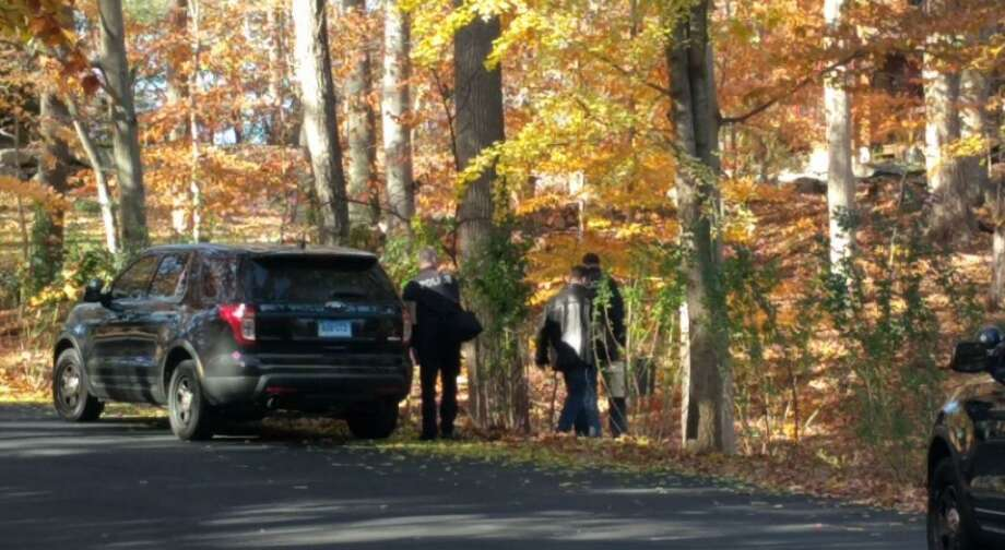 Greenwich police officers investigate a wooded area off Old Stone Bridge Road Saturday, the scene of a reported death. Photo: Cedar Attanasio / Hearst Connecticut Media / Greenwich Time