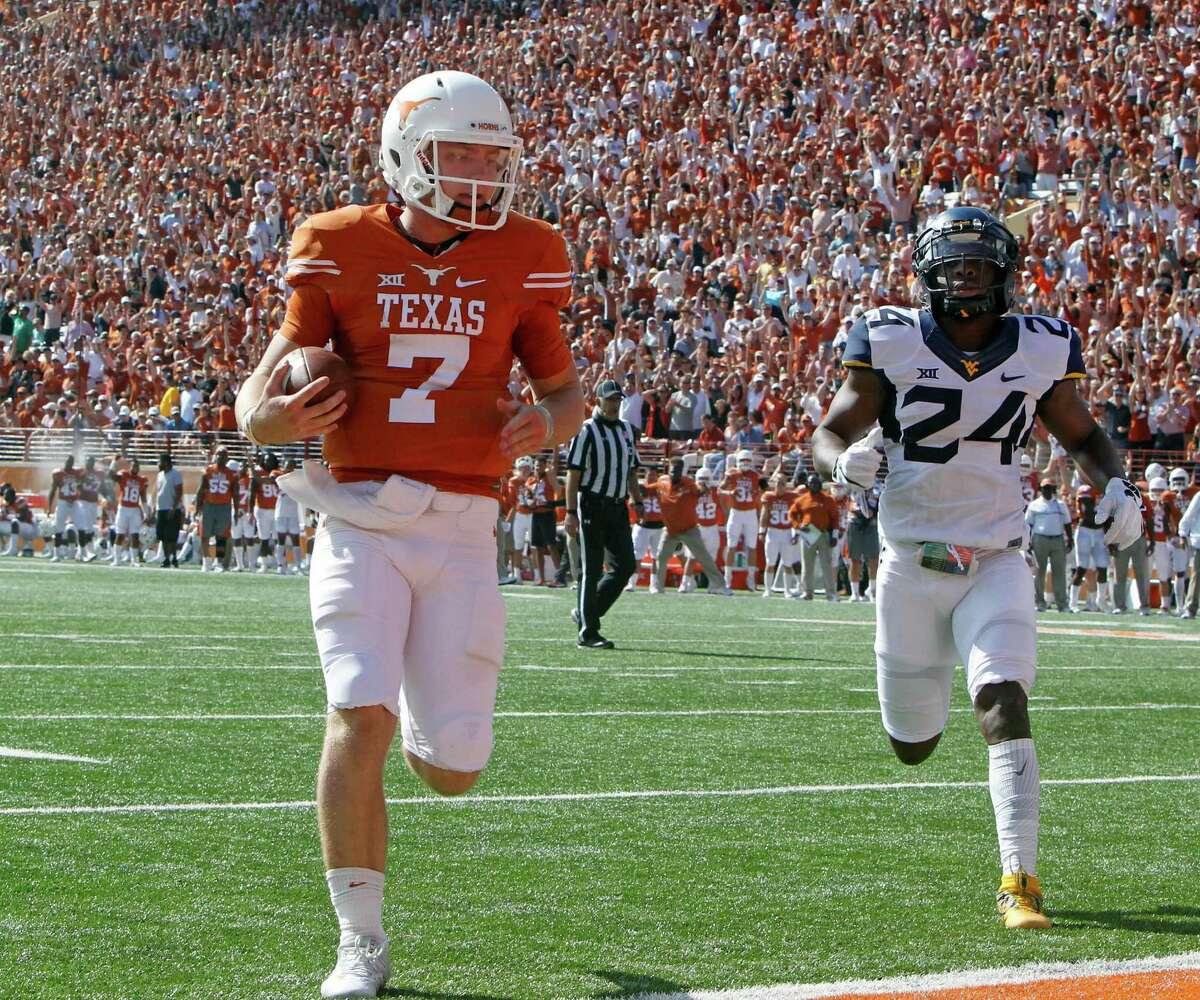 Texas quarterback Shane Buechele (7) runs for a touchdown against West Virginia cornerback Maurice Fleming (24) during the first half of an NCAA college football game, Saturday, Nov. 12, 2016, in Austin, Texas. (AP Photo/Michael Thomas)