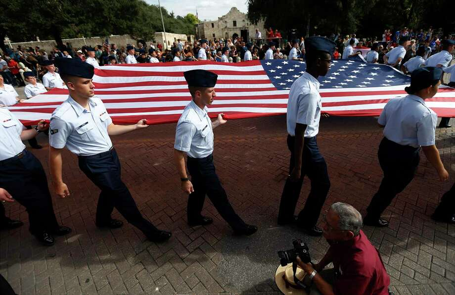 The American flag is presented in front of the Alamo during the annual Veterans Day parade downtown. Photo: Photos By Kin Man Hui / San Antonio Express-News / ©2016 San Antonio Express-News