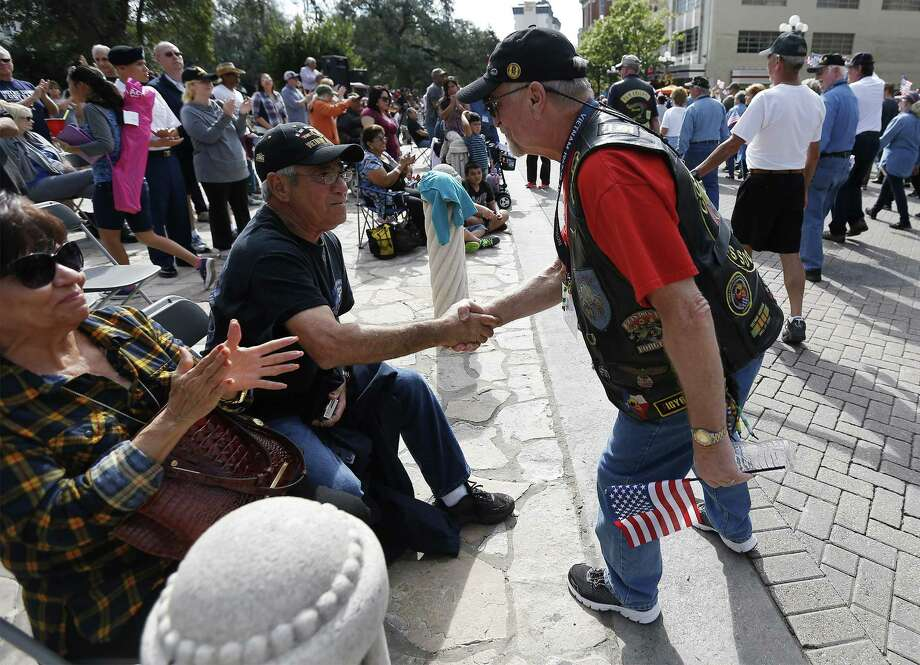 """Vietnam veteran Eliseo Garza (left) receives a handshake while watching the annual Veteran's Day parade in downtown on Saturday, Nov. 12, 2016. Military veterans were honored with a parade through downtown San Antonio as parade watchers waved flags and said """"thank you"""" aloud to active and retired military who took part in the parade. (Kin Man Hui/San Antonio Express-News) Photo: Kin Man Hui, Staff / San Antonio Express-News / ©2016 San Antonio Express-News"""