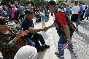 """Vietnam veteran Eliseo Garza (left) receives a handshake while watching the annual Veteran's Day parade in downtown on Saturday, Nov. 12, 2016. Military veterans were honored with a parade through downtown San Antonio as parade watchers waved flags and said """"thank you"""" aloud to active and retired military who took part in the parade. (Kin Man Hui/San Antonio Express-News)"""