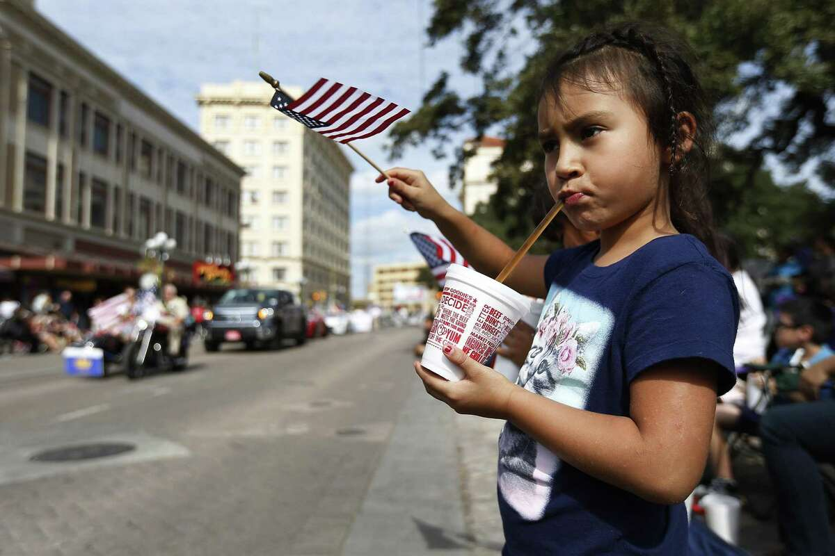 """Divinity Muniz, 6, sips on a drink while waving her American flag during the annual Veteran's Day parade in downtown on Saturday, Nov. 12, 2016. Military veterans were honored with a parade through downtown San Antonio as parade watchers waved flags and said """"thank you"""" aloud to active and retired military who took part in the parade. (Kin Man Hui/San Antonio Express-News)"""