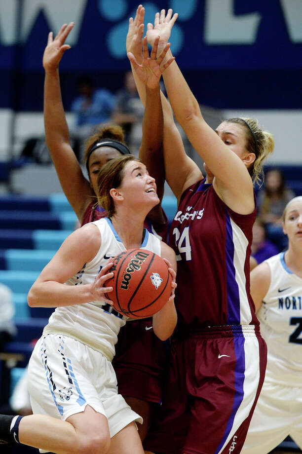 Northwood's Ashley Campbell, center, drives to the basket as Saint Joseph's Rolanda Curington, left, and Abbey Titzer, right, defend during the second quarter on Saturday at Northwood University. The Timberwolves won 64-58. Photo: NICK KING | Nking@mdn.net