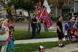Men wave Confederate flags Friday in Petaluma's Walnut Park while bystanders gather to watch the annual Veterans Day parade.