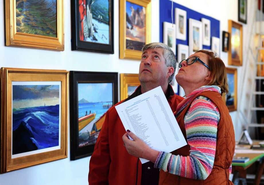 Bob Dickinson, of Brookfield, and friend Audrey Latouf, of Milford, check out art by Brechin Morgan during the Bridgeport Arts Trail Open Studios at the former American Fabric complex on Saturday. Nov. 12, 2016. In its 11th year, American Fabrics Arts Building (AFA) Open Studios showcases over 25 artists in their studios where the creative process happens. Held in a renovated factory building where linen and lace were once manufactured, the event has become a destination for collectors, interior designers, and art lovers alike. Photo: Christian Abraham / Hearst Connecticut Media / Connecticut Post