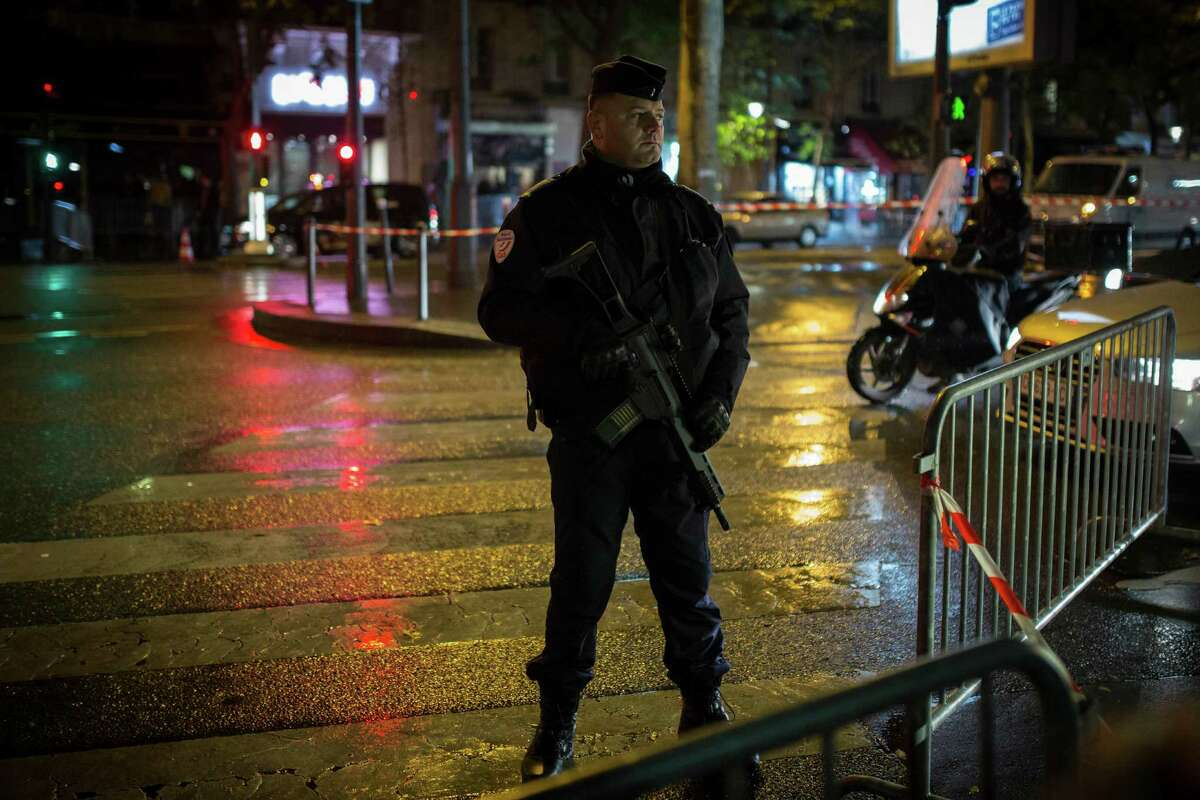 A riot police officer stands guard near the Bataclan concert hall in Paris, Saturday, Nov. 12, 2016. A concert by British pop legend Sting is marking the reopening of the Paris' Bataclan concert hall one year after suicidal jihadis turned it into a bloodbath and killed 90 revelers. The coordinated attacks in Paris on Nov. 13 last year that also targeted bars, restaurants and the sports stadium, leaving 130 people dead. (AP Photo/Kamil Zihnioglu)
