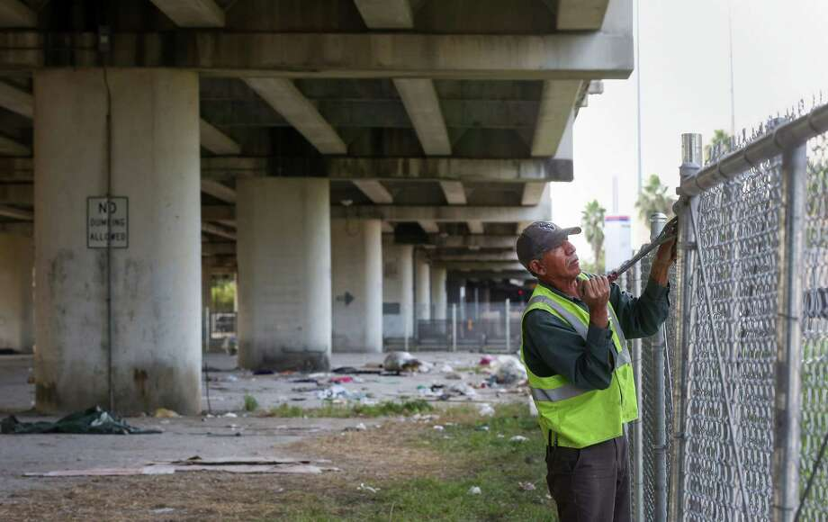 Workers erect a fence around an underpass where a homeless camp previously existed near  Wheeler Avenue and Fannin Street. Photo: Jon Shapley, Staff / © 2015  Houston Chronicle