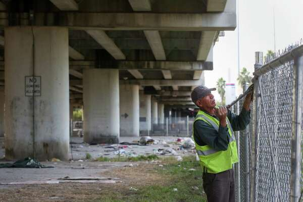 Workers erect a fence Friday around an underpass where a homeless camp previously existed near  Wheeler Avenue and Fannin Street. That area was a hot spot for the use of synthetic marijuana.