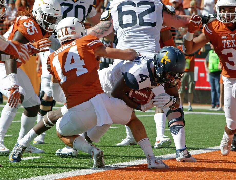 West Virginia running back Kennedy McKoy (4) runs for a touchdown against Texas' Dylan Haines (14) during the first half of an NCAA college football game, Saturday, Nov. 12, 2016, in Austin, Texas. (AP Photo/Michael Thomas) Photo: Michael Thomas, FRE / FR65778 AP