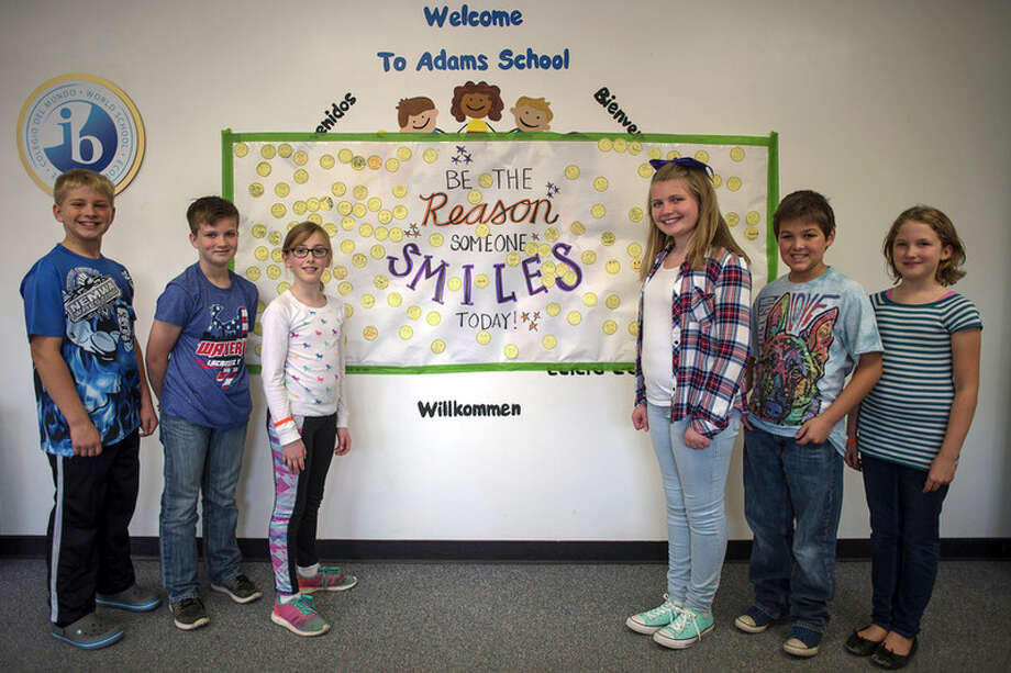 ERIN KIRKLAND | ekirkland@mdn.net From left, fifth graders Merrick Hocking, 11, Eli Elza, 10, Isla McCubein-Green, 10, Addison Rogers, 10, Luke McMahan, 10, and Hannah Wejrowski, 10, stand in front of the 'Be the Reason Someone Smiles Today' mural on Thursday at Adams Elementary. The group was in charge of the mural which was part of the Week of Nonviolence. / Midland Daily News