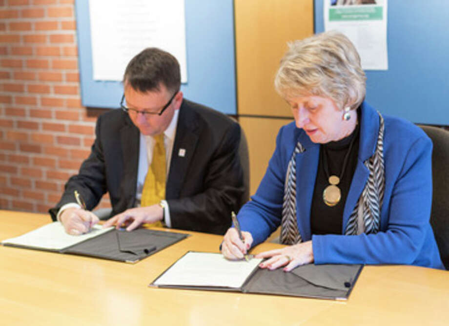 LSSU Interim Provost David Roland Finley and Delta College President Jean Goodnow sign an agreement.