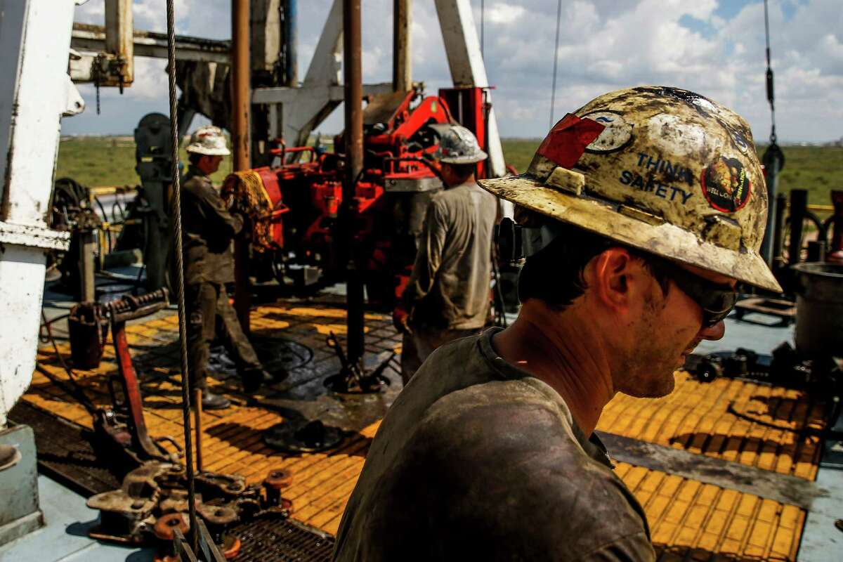 Helmerich & Payne floor hand Jeremy Lewellyan, right, operates controls to add a section of pipe as they drill for oil and gas on a Diamondback Energy lease Wednesday, Sept. 14, 2016 outside of Midland. ( Michael Ciaglo / Houston Chronicle )