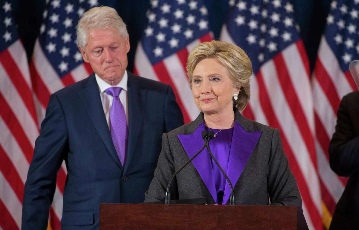 FILE -- Hillary Clinton, accompanied by Bill Clinton, gives a concession speech before campaign staff and supporters at the New Yorker hotel in Manhattan, Nov. 9, 2016. The decision by Donald Trump on whether to further investigate Hillary Clinton will signal if he intends to look ahead and Â?