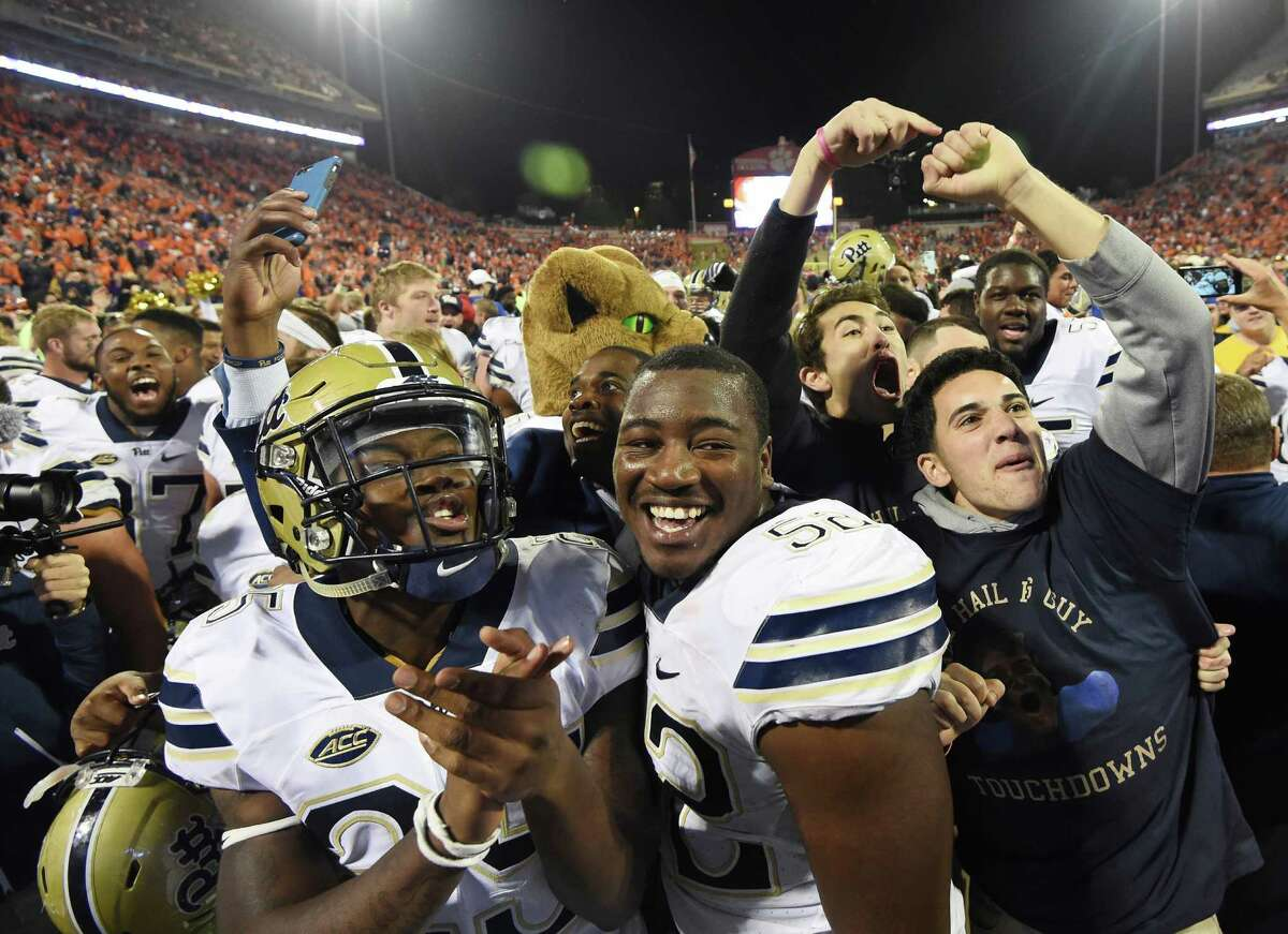 Pittsburgh's Elijah Zeise, left, and Shakir Soto celebrate with fans on the field after beating No. 2 Clemson on Saturday.