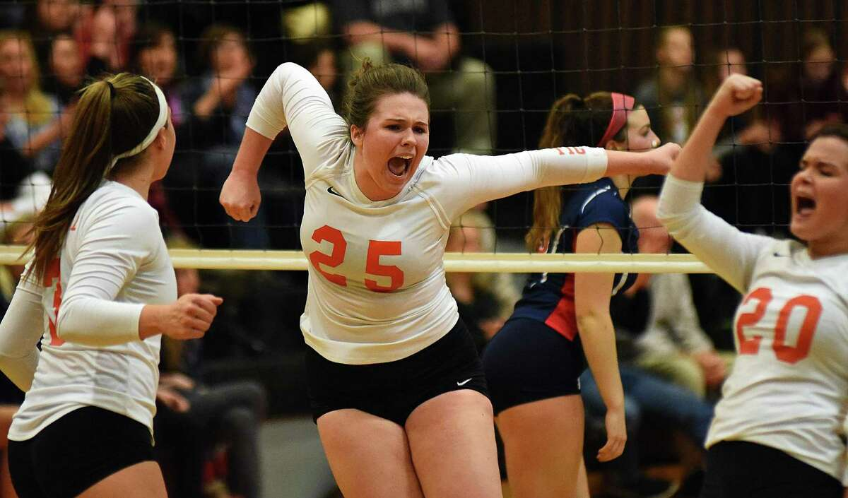 Ridgefield's Elizabeth Middlebrooks, center, reacts with teammates Caroline Curnal, left, and Kathryn Linekin, right, following a point during Saturday afternoon's CIAC Class LL girls volleyball quarterfinal match against Brien McMahon in Ridgefield. The Tigers held on for a 3-2 win.