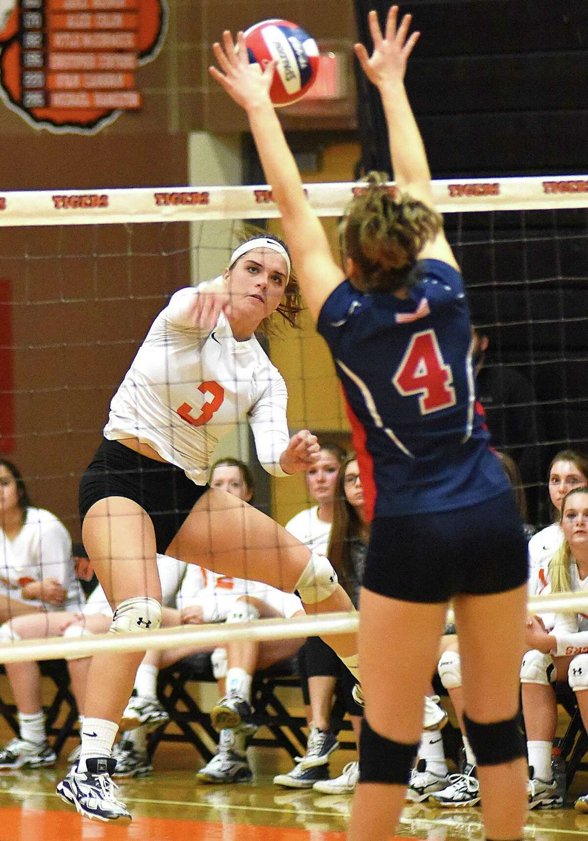 Ridgefield's Caroline Curnal, left, fires a shot past Brien McMahon's Julita Przybylska during Saturday afternoon's CIAC Class LL girls volleyball quarterfinal match against Brien McMahon in Ridgefield. The Tigers held on for a 3-2 win.