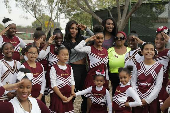 CORRECTS PARK SPELLING TO LUEDERS, NOT LEUDERS - Serena Williams, center left, and sister, Venus, pose with the members of the Compton Sounders drill team after attending a dedication ceremony of the Lueders Park tennis courts Saturday, Nov. 12, 2016, in Compton, Calif. The courts were dedicated in their name. (AP Photo/Jae C. Hong)