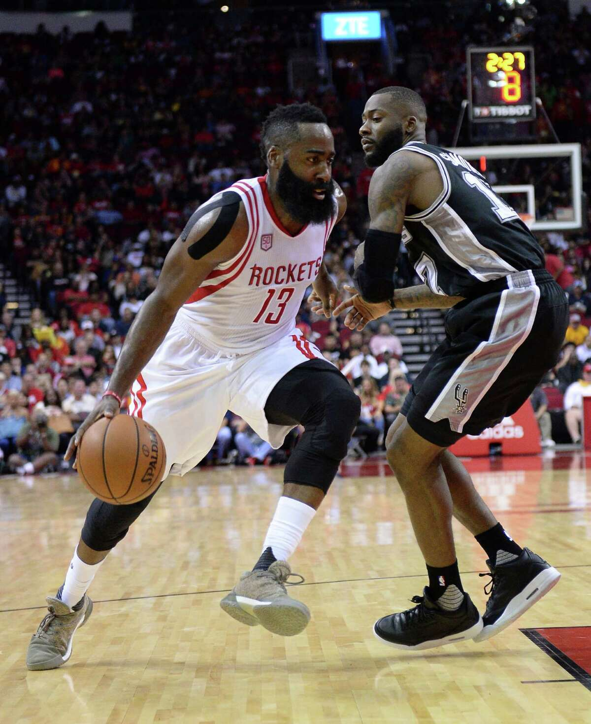 Houston Rockets guard James Harden (13) drives against San Antonio Spurs forward Jonathon Simmons (17) in the first half of an NBA basketball game on Saturday, Nov. 12, 2016, in Houston. (AP Photo/George Bridges)