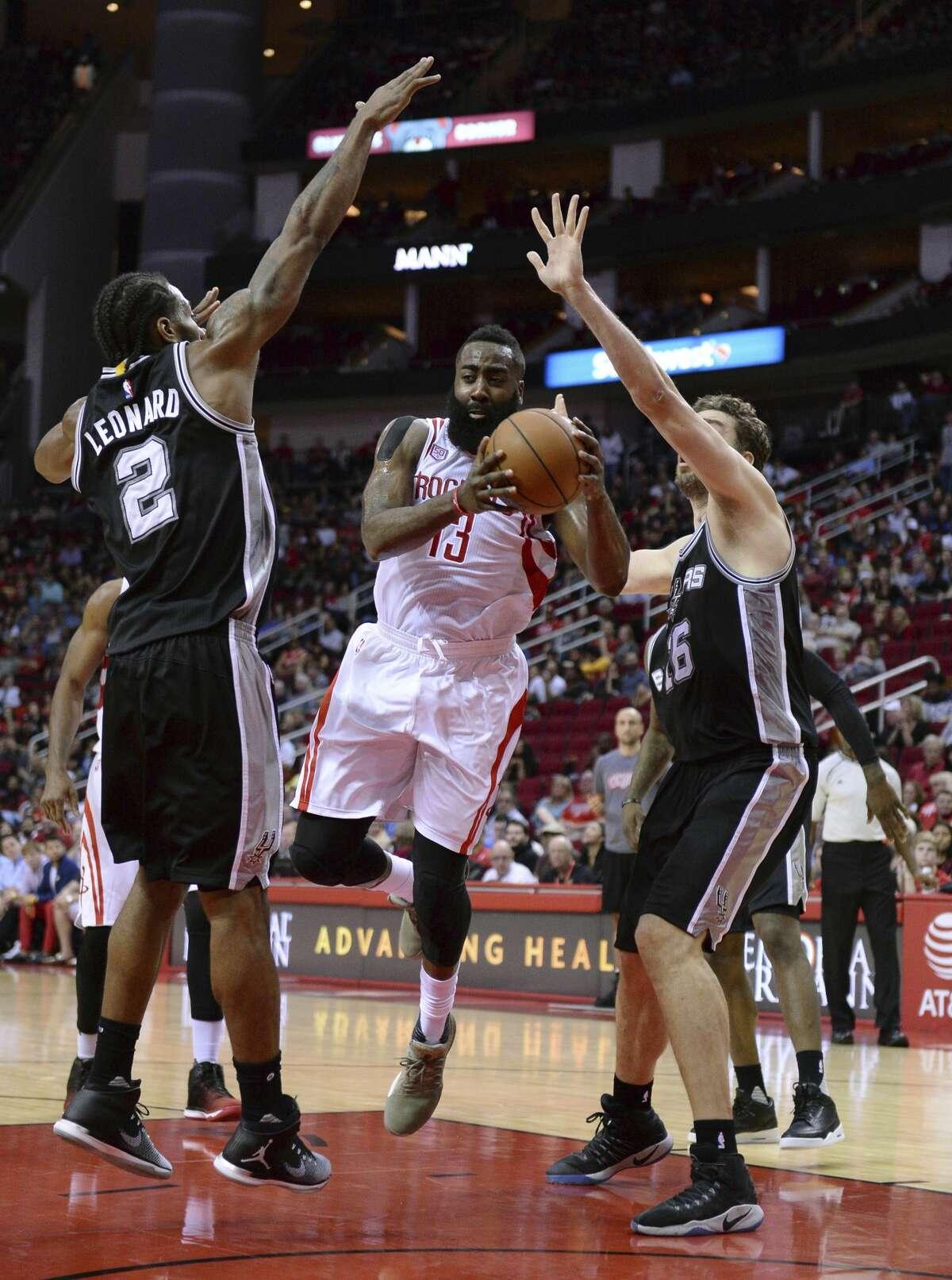 Houston Rockets guard James Harden (13) looks to pass against San Antonio Spurs forward Kawhi Leonard (2) and Pau Gasol (16) in the first half of an NBA basketball game on Saturday, Nov. 12, 2016, in Houston. (AP Photo/George Bridges)