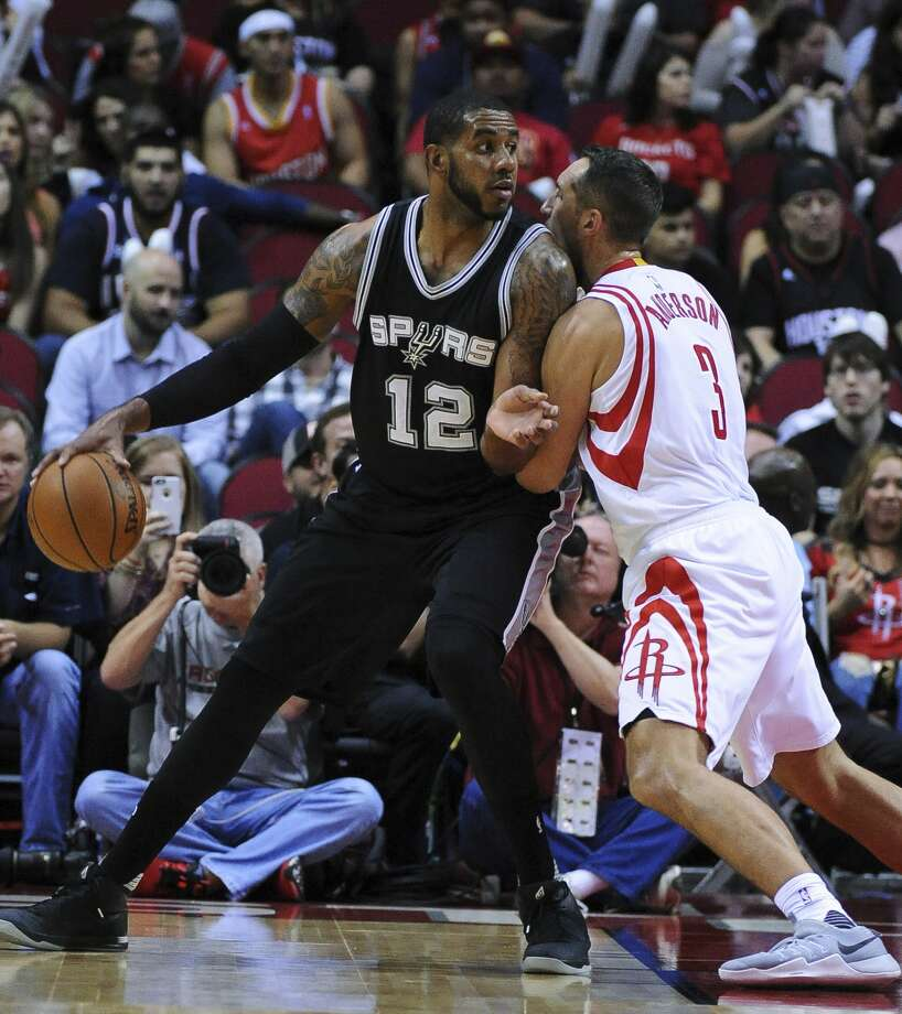 San Antonio Spurs forward LeMarcus Aldridge (12) is closely guarded by Houston Rockets forward Ryan Anderson (3) in the first half of an NBA basketball game on Saturday, Nov. 12, 2016, in Houston. (AP Photo/George Bridges) Photo: George Bridges/Associated Press