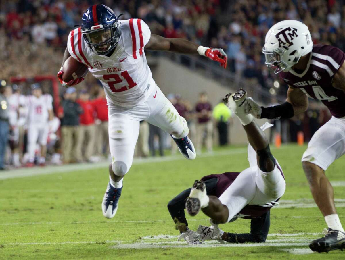 Mississippi running back Akeem Judd (21) jumps over a Texas A&M defender during the first quarter of an NCAA college football game Saturday, Nov. 12, 2016, in College Station, Texas. (AP Photo/Sam Craft)
