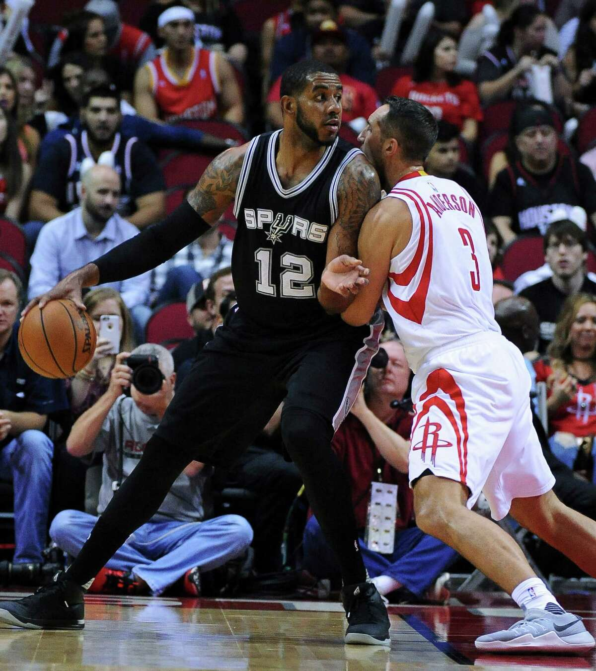 San Antonio Spurs forward LeMarcus Aldridge (12) is closely guarded by Houston Rockets forward Ryan Anderson (3) in the first half of an NBA basketball game on Saturday, Nov. 12, 2016, in Houston. (AP Photo/George Bridges)