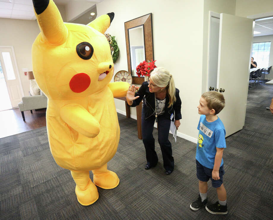 Terri Jaggers, Executive Director of Hope's Path, encourages a young visitor to high five Pikachu during the Pokemon Go themed open house for Hope's Path on Saturday. Photo: Michael Minasi, Staff / © 2016 Houston Chronicle