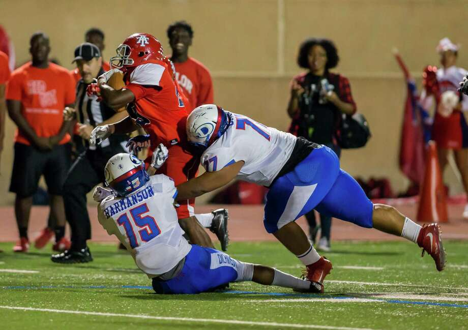 Dickinson Gators Trevor Harmanson (15) and Dickinson Gators Keelan Oatis (77) tackle Alief Taylor Lions Darnell Harris (29) during the 6A Division 1 playoff game between Alief Taylor and Dickinson at LeRoy Crump Stadium on November 12, 2016 in Houston, Texas.  (Leslie Plaza Johnson/Freelance) Photo: Leslie Plaza Johnson, For The Chronicle / Freelance